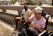 Princetta Dwyer (R), 82, waits on a highway overpass after being rescued from a flooded area in New Orleans August 30, 2005.  The historic city of New Orleans was steadily filling with water from nearby Lake Ponchartrain on Tuesday after its defenses were breached by the ferocity of hurricane Katrina.   REUTERS/Rick Wilking