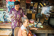 "11 JANUARY 2013 - BANGKOK, THAILAND:     A woman has hair colored while she tends her shop in the Ban Krua neighborhood in Bangkok. The Ban Krua neighborhood of Bangkok is the oldest Muslim community in Bangkok. Ban Krua was originally settled by Cham Muslims from Cambodia and Vietnam who fought on the side of the Thai King Rama I. They were given a royal grant of land east of what was then the Thai capitol at the end of the 18th century in return for their military service. The Cham Muslims were originally weavers and what is known as ""Thai Silk"" was developed by the people in Ban Krua. Several families in the neighborhood still weave in their homes.      PHOTO BY JACK KURTZ"