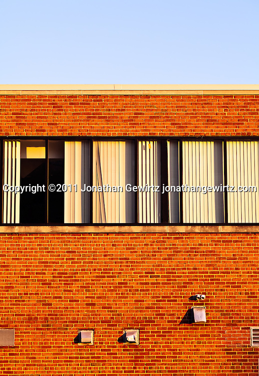 Exterior wall and windows in a section of the top floor of a small brick office building. WATERMARKS WILL NOT APPEAR ON PRINTS OR LICENSED IMAGES.