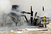 Jackson Hole Fire/EMS sprays foam on a smouldering Amerigas on High School Road on Friday afternoon after an explosion at the propane filling station.
