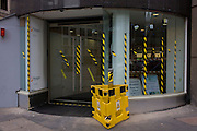 Yellow and black hazzard tape on the window of a City of London business.