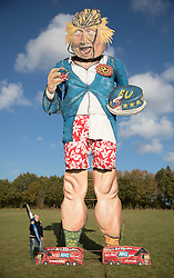 © Licensed to London News Pictures. 31/10/2018. Edenbridge, UK. Artist Andrea Deans stands next to an effigy of former foreign secretary Boris Johnson as it is unveiled in Edenbridge, Kent ahead of its burning at the town's bonfire this Saturday. The 10 meter high figure stands over two EU referendum buses and Boris is also carrying an EU cake. Photo credit: Peter Macdiarmid/LNP