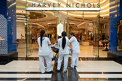 Female maids wait outside Harvey Nichols store in the Prestige mall inside The Avenues shopping mall in Kuwait City, Kuwait.