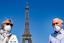 Tourists wearing protective masks pose in front of the Eiffel Tower in Paris, France on April 12, 2020. France's overall death toll from the coronavirus has risen to nearly 14,400 - but for the fourth day in a row, slightly fewer people were admitted into intensive care.The French president is expected to announce the lengthening of a country-wide lockdown which began on March 17 and were renewed two weeks later. Photo by Robin Utrecht/ABACAPRESS.COM