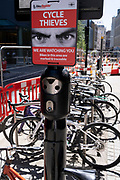 A crime prevention warning sign aimed at bike thieves, warns of being watched in an effort to cut the theft of property from cycling commuters, in the City of London, the capital's financial district, on 8th June 2021, in London, England.