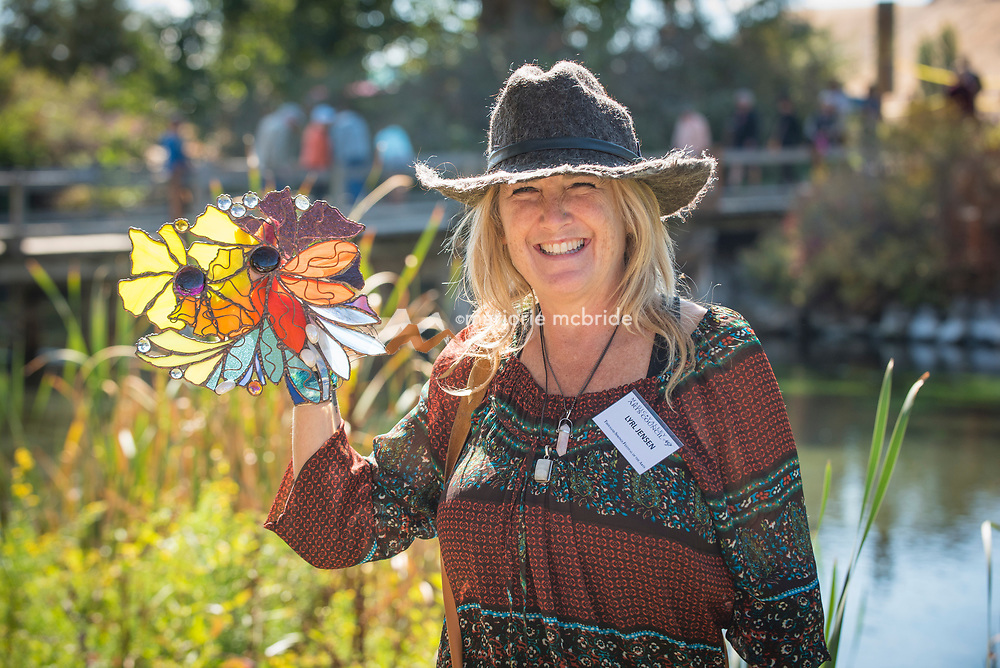 Artist Lyrl Jensen holding a piece of her stain glass art work during the Thousand Springs Art Festival at Ritter Island near Hagerman, Idaho. VRM