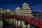"Lit at night, Matsumoto Castle reflects in the moat by its red bridge. The castle was built from 1592-1614 in Matsumoto, Nagano Prefecture, Japan. Matsumoto Castle is a ""hirajiro"" - a castle built on plains rather than on a hill or mountain, in Matsumoto. Matsumotojo's main castle keep and its smaller, second donjon were built from 1592 to 1614, well-fortified as peace was not yet fully achieved at the time. In 1635, when military threats had ceased, a third, barely defended turret and another for moon viewing were added to the castle. Interesting features of the castle include steep wooden stairs, openings to drop stones onto invaders, openings for archers, as well as an observation deck at the top, sixth floor of the main keep with views over the Matsumoto city."