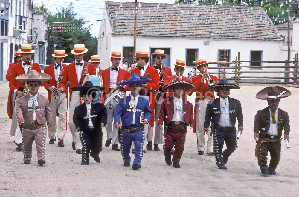 """The dwarf troupe of """"torero"""" bullfighter Guillermo Gomez walk through the town of Cienpozuelo  to generate interest in the afternoon bullfights at the local ring, in tow a band of musicians, Spain."""