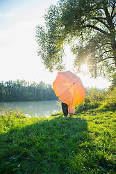 Couple standing behind sunshade at riverbank against Sunlight, Bavaria, Germany