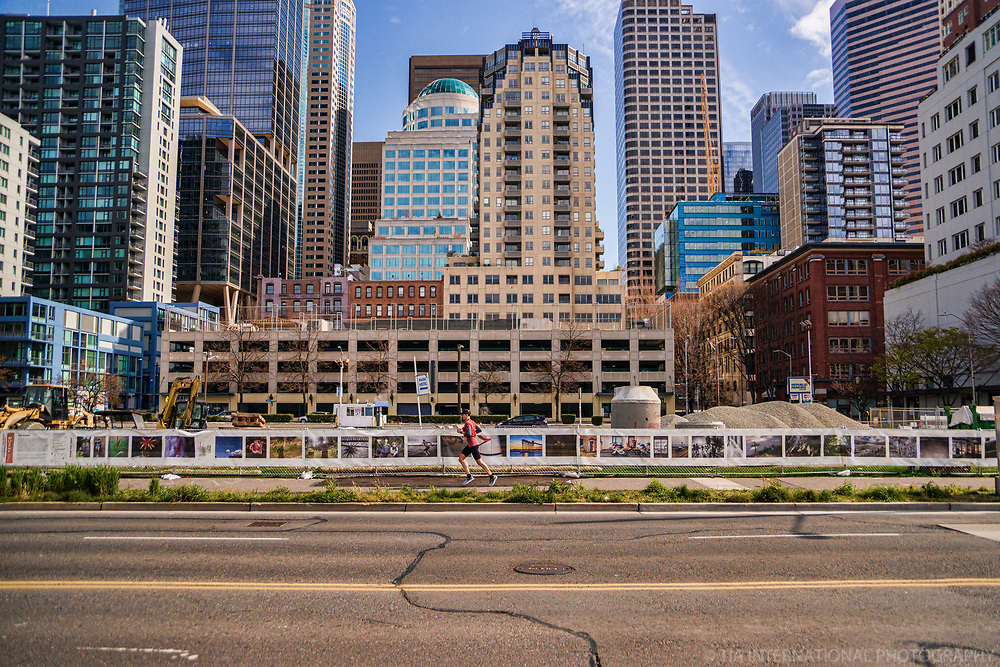 A man jogs along a pathway next to a fence of artwork separating him from the empty construction site for Seattle's Waterfront renovation project. (April 4, 2020).