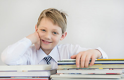 Portrait of boy with stack of books, smiling