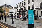 A Covid-19 public health information sign is pictured in front of local residents enjoying refreshments outside a JD Wetherspoon public house on 27th July 2021 in Maidenhead, United Kingdom. JD Wetherspoon chairman Tim Martin has complained of labour shortages at the chains pubs due to 5,000 of his 40,000 staff having to self-isolate after having been contacted by NHS Test and Trace.