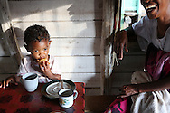 """Albertine Sampy, 41, left, laughs while feeding her 2 year old granddaughter Elshyrah, at their home in Brickaville, Madagascar. """"We had to fight against death,"""" says Albertine  of Cyclone Giovanna. The brutal winds that tore off the roof of her house and destroyed 60 lychee trees that produced 1.5 tons of fruit each year. Coupled with the loss of her rice fields Albertine lost 80 percent of her income and calculates it will take at least 5 years for her trees to begin producing again and for life to resume to normal. Sara A. Fajardo/Catholic Relief Services"""