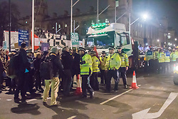 Westminster, London, December 2nd 2015.  As Parliament prepares to vote on air strikes on Islamic State terrorists in Syria, Stop The War and other groups opposed to British military involvement protest outside Parliament. PICTURED: Police surround a truck under which peace protester Maria Gallastegui had crawled, bringing Parliament Square traffic chaos. ///FOR LICENCING CONTACT: paul@pauldaveycreative.co.uk TEL:+44 (0) 7966 016 296 or +44 (0) 20 8969 6875. ©2015 Paul R Davey. All rights reserved.