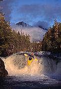The late American expeditionary kayaker Lars Holbeck runs a waterfall on Davis Creek as the evening sun breaks through parting mist on the Seward Penninsula, Alaska.