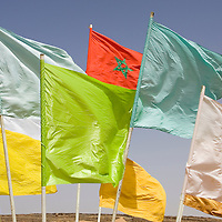 24 March 2007:  Morocco red and green national banner is raised among others flags the day before the beginning of the 22nd Marathon des Sables, a 6 days and 151 miles endurance race with food self sufficiency across the Sahara Desert in Morocco. Each participant must carry his, or her, own backpack containing food, sleeping gear and other material.