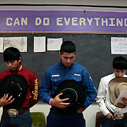 Nathan Losoya, left, 16, Joel Garcia, 17, and Arnold Guzman, 14, remove their hats while conducting a prayer before their weekly club meeting in coach Frank Quesada's Weslaco High School art room. The club meets once a week to discuss what rodeos they will compete in around south Texas. <br /> Nathan Lambrecht/The Monitor