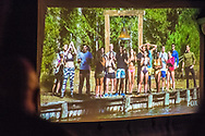 """Merrick, New York, USA. 11th June 2017.  During """"American Grit"""" Season 2 premiere, (4th from right in blue swim trunks) CHRIS EDOM, 48, of Merrick, is one of 17 contestants getting ready for a lake water endurance challenge. Show was projected on large screen during Edom's backyard Viewing Party for Episode 1 of FOX network reality television series. Edom was last contestant picked for a team that episode."""