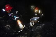 Dos mineros trabajan dentro de un socavón de la mina en Rinconada, el calor y la humedad hacen que el trabajo sea muy duro.<br /> <br /> Two miners work inside a tunnel of the mine of Rinconada, the heat and humidity makes the work very hard.