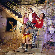 4 happy teens two male and two female, in a fashion style shot in an old dilapidated environment