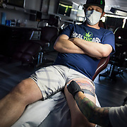 """Jamie owns a tattoo studio and is working behind locked doors in violation of the city's Safer At Home order as a """"non-essential"""" business. His income is down 50% and he said he'd be in terrible shape if he stopped working and would have to try to sell artwork instead. He said he applied for the PPP money but never received anything."""