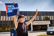 22 AUGUST 2020 - DES MOINES, IOWA: JONATHON EAST, from Saylor Township, stands  in front of the main US Post Office in Des Moines during a rally in support of the USPS. About 35 people picketed the main US Post Office in Des Moines Saturday protesting changes made to the Postal Service by the Trump Administration. Nationally, there has been concern that changes to the Postal Service will hurt citizens' ability to vote by mail in the 2020 presidential election.         PHOTO BY JACK KURTZ