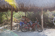 Tulum, Mexico - May 08, 2021: A couple takes a break during their bicycle ride between Tulum town and the hotel zone.