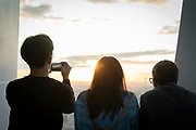 Three tourists looking at London cityscape at sunset, London, England, UK