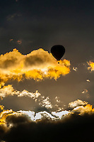 Hot air balloons flying through the clouds at sunrise, Albuquerque International Balloon Fiesta, Albuquerque, New Mexico USA.