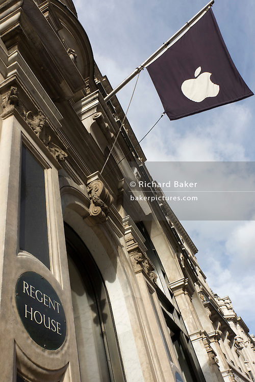 Looking up at the corporate flag of Apple's logo on a banner high above street level at Regent House (1898) in London's Regent's Street. This Apple Store was the first to be built in Europe and serves as a flagship outlet for the stylish brand of computer accessories that were largely the brainchild of Steve Jobs (1955-2011) who started the company as a student in 1977.