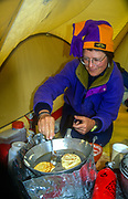 Sue Werner cooks pancakes, Chongtar base camp, above Sarpo Laggo glacier, Karakoram mtns, far western China, Cntral Asia.
