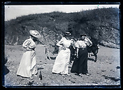 women having a good time and drinking champagne while on the beach France ca 1910s