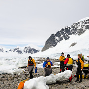 A group of kayakers take a shore break on the rocky beach at Cuverville Island on the Antarctic Peninsula.
