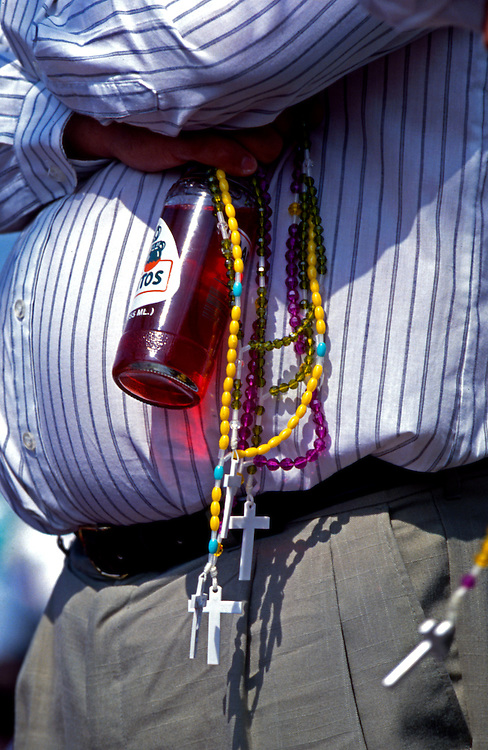 A pilgrim holds rosaries and a Mexican soft drink.<br /> From October 13, 1990, through October 13, 1998, Conyers, Georgia housewife Nancy Fowler claimed that the Virgin Mary appeared to her and relayed messages to all citizens of the United States. The messages ranged from admonitions to prayers to warnings of war. The Virgin's supposed visits to Conyers, a suburban community about thirty miles east of Atlanta, make Conyers one of the longest-lived Marian apparition sites in the nation.<br /> In the early 1990s the roads to Conyers were clogged with pilgrims yearning to hear Mary's message. They came from every direction, but most were from heavily Hispanic southern Florida. They headed toward a large field adjacent to Fowler's home. Once there, they prayed on Mary's Holy Hill, filled bottles with water from the Blessed Well, or visited the small bookstore on the property.<br /> At midday the pilgrims moved toward Fowler's farmhouse. Inside, Fowler waited for a message from the Virgin Mary in the Apparition Room; outside, members of Our Loving Mother's Children, the volunteer group that organized the Conyers gatherings, led the crowd in song and in prayer. The pilgrims prayed in their native tongues, including English, Spanish, Russian, and Chinese. When Mary's message was broadcast over loudspeakers, the pilgrims raised their rosaries, icons, and petitions heavenward, hoping the items would be blessed by the presence of the Virgin Mary. Some claimed miracles at this site—rosaries turning to gold, the sun spinning and changing colors, and the scent of rose petals filling the air.