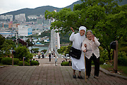 A nun guiding an elderly woman to a mountain top during an organised excursion for old people to the city of Yeosu.  / South Korea, Republic of Korea, KOR, 24th of May 2010.