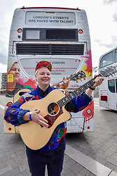 © Licensed to London News Pictures. 21/07/2017. London, UK. Musician Kal Lavelle performs in front of a bus with featuring her image ahead of Dire Straits frontman Mark Knopfler unveiling two iconic London buses outside Wembley Stadium to celebrate launch of Gigs, in association with Gibson, on the eve of International Busking Day. The buses feature pictures of artists Kal Lavelle, Jay Johnson and Modupe Obasola who have all taken part in the Mayor of London's annual busking competition.    Photo credit : Stephen Chung/LNP