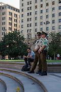 Police stand guard with a bystander at the Plaza de la Constitucion, Santiago, Chile.