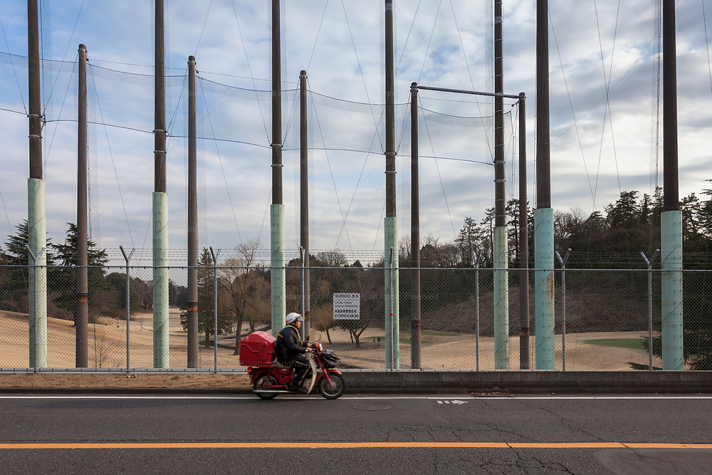 A postman on a motorbike  rides past tall fences surrounding the golf course on the Naval Air Facility, Atsugi airbase near Yamato, Kanagawa, Japan, Wednesday February 13th 2019
