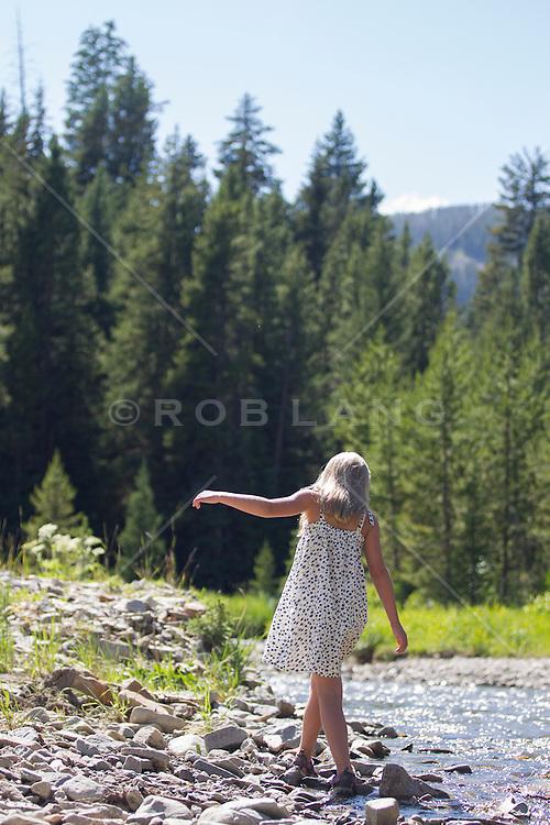 little blonde girl walking by a stream in Montana
