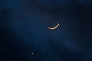 The crescent moon and the planets Venus (bottom) and Mars form a conjunction in the sky just after sunset on February 20, 2015.
