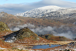 © Licensed to London News Pictures. 20/01/2019. Lake District, UK. People enjoy the view from the summit of Loughrigg Fell, in the Lake District as the surrounding mountains are covered in snow and fog fills the valleys during cold weather. Photo credit : Tom Nicholson/LNP