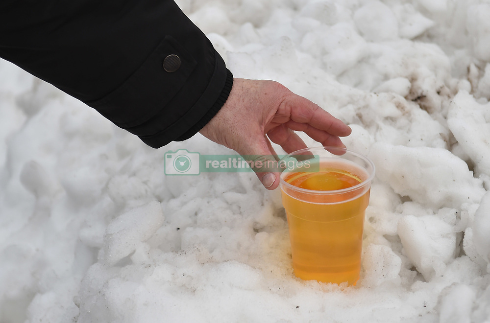 A Bristol City fan makes use of the snow to keep his pint of beer cold before the game.