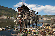 A naked Haitian boy stands near a public latrine, located in a polluted section of the destitute community of Shada. Cap Haitian, Haiti, January 28, 2008.
