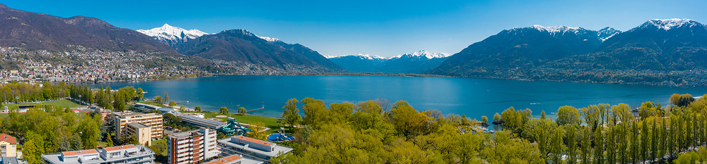 Aerial view of Lago Maggiore from Locarno, surround by mountain with green trees and snow. Sunny day of spring