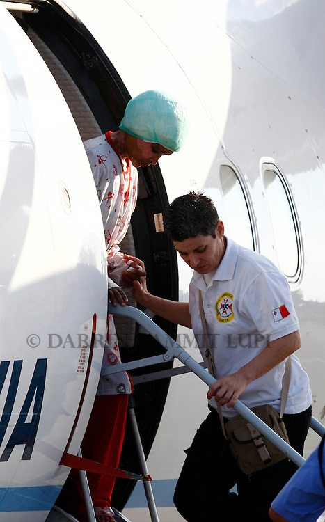 Shwejga Mullah (L) of Ethiopia is helped off a plane after arriving at Malta International Airport,outside Valletta September 15, 2011. An Ethiopian nanny in the Gaddafi household who suffered horrific burns after she did not stop one of Muammar Gaddafi's grandchildren crying, has arrived in Malta for specialised medical treatment. Shwejga Mullah was recently discovered weak and alone in the home abandoned by Muammar Gaddafi's son Hannibal. She said that  Hannibal Gaddafi's wife Aline threw boiling water over her when she did not stop Hannibal Gaddafi's daughter crying and refused to beat the child. The nanny was brought over in a private plane chartered by the Maltese government.    REUTERS/Darrin Zammit Lupi (MALTA)