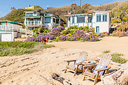 Two Wood Adirondack Chairs on the Beach in Front of Crystal Cove Beach Cottages