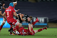 Olly Cracknell of the Ospreys © is stopped by Aaron Shingler, Tadhg Beirne (8) and Will Boyde (7) of the Scarlets. Guinness Pro14 rugby match, Ospreys v Scarlets at the Liberty Stadium in Swansea, South Wales on Saturday 7th October 2017.<br /> pic by Andrew Orchard, Andrew Orchard sports photography.