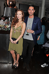 OLIVIA GRANT and HUGO TAYLOR at the opening of the 'pop up' Tanqueray Gin Palace hosted by Idris Elba at 13 Floral Street, Covent Garden, London on 26th March 2013.