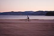 A man rides his bicycle along the beach at Playa Santispac, Baja California Sur, Mexico.