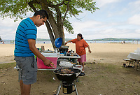 Omar Garcia and Ana Gonzelas cook up some steaks and spanish rice at Endicott Rock Park on Weirs Beach with family from Chelsea, MA and Brooklyn, NY on Saturday.   (Karen Bobotas/for the Laconia Daily Sun)